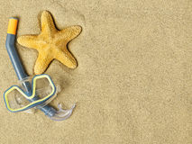 Starfishes and swimming goggles on sand Stock Images