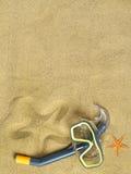 Starfishes und Schwimmenschutzbrillen auf Sand Stockfotografie