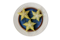 Starfruit on blue and white plates. Three pieces of starfruit (Carambola) on blue and white plates Royalty Free Stock Photo