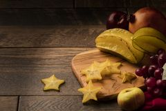 Starfruit on wooden table with grapes, apple, and pomegranate Stock Photos