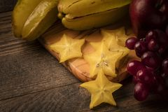 Starfruit on wooden table with grapes, apple, and pomegranate Royalty Free Stock Images
