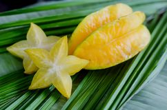 Starfruit, Carambola on green leaf. Sliced carambola fruit on green palm leaf Royalty Free Stock Photography