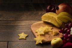 Starfruit på trätabellen med druvor, äpplet och granatäpplet Arkivfoton