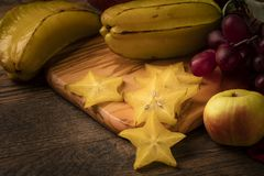 Starfruit on wooden table with grapes, and apple Stock Photos