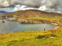 Staring into the bay and cliffs. On Achill Island on the west coast of Ireland in county mayo, a lone woman looks at the beauty of the Irish landscape and the Stock Image