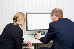 Staring at blinds. Two colleagues staring at a monitor with blinds in a blinded office Royalty Free Stock Photos