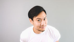 Staring at the camera. An asian man with white t-shirt and grey background royalty free stock image
