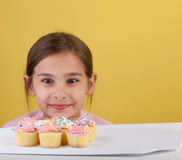 Staring cross eyed at a cupcake. Young girl staring cross eyed at a bunch of cupcakes  on a yellow background Royalty Free Stock Photo