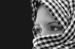 Staring into darkness. Black and white portrait of a young woman wearing a shawl wrapped around her head Stock Image