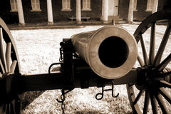 Staring down the barrel of history. An old cannon from colonial days (civil war and earlier) at historic Fort Washington. Officer's barracks in background Stock Photo