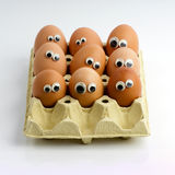 Staring eggs in a box. A group of eggs in a box with funny eyes stock image