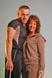 Staring fitness couple. Athletic   couple mature and looking at the camera Isolated on a drab blue background she's got curly hair and is wearing a hooded sweat Stock Photography