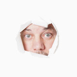 Staring through hole. Male eyes staring through torn hole voyeurism or stalking concept Stock Photo