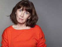 Staring mature woman looking under shock for winter season Stock Photos