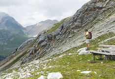 Staring into the Mist. A hiker studies the landscape near a resting bench built high up in the alpine regions of the Dolomite Mountains in Northern Italy Royalty Free Stock Photos