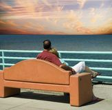 Staring at the sea. Middle aged couple sitting on a bench and looking out to the ocean at a sunset Royalty Free Stock Images
