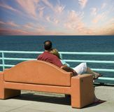 Staring at the sea. Middle aged couple sitting on a bench looking at the sea and sunset Royalty Free Stock Photos