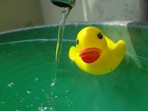 Staring of the tap. Yellow duck toy staring of the tap Royalty Free Stock Images