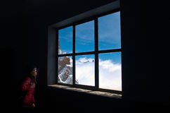 Staring at the window. Woman in the dark staring at a blue sky through a window Royalty Free Stock Image