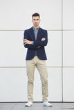 Staring young business man standing with arms crossed. Full body portrait of staring young business man standing with arms crossed Royalty Free Stock Photos