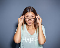 Staring young woman looking over glasses. Pressing her lips together Royalty Free Stock Photos