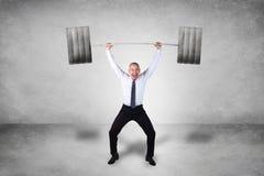 Stark affärsman Lifting Heavy Weight arkivbild