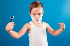 Stark allvarlig ung pojke, i att raka skum som man arkivfoton