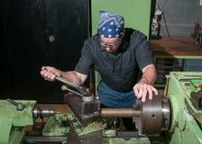 Stark bei der Arbeit in einer Maschinenwerkstatt. Lizenzfreies Stockbild