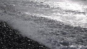 Stark bränning på den pebbly stranden med stora vågor på bakgrunden av inställningssolen stock video