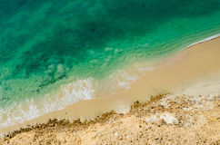 Stark contrast of beautiful turquoise blue ocean meeting yellow beach. Taken from the cliffs above in Caotinha, Angola Royalty Free Stock Photo