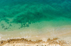 Stark contrast of beautiful turquoise blue ocean meeting yellow beach. Taken from the cliffs above in Caotinha, Angola Stock Images