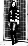 Stark contrast in photo of young woman of her horizontal striped sweater against grid background in this black and white image. A lovely lady stands in front of stock images