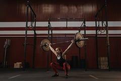 Stark crossfitkvinna som gör squats med skivstångfast utgift Färdig ung kvinna som lyfter tunga vikter royaltyfri foto