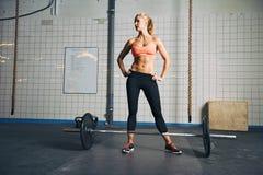 Stark crossfitkvinnlig på idrottshallen med skivstånger Arkivfoton