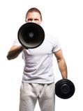 Stark, färdig och sportig kroppsbyggareman som skriker med en megafon Royaltyfri Foto