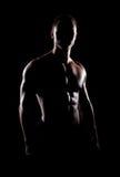 Stark, färdig och sportig kroppsbyggareman över svart bakgrund Fotografering för Bildbyråer