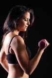 stark härlig idrottshall för flicka för bicepkrullningsövning royaltyfria foton