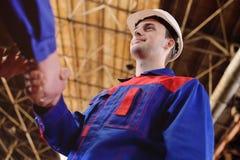 Stark handskakning av män i overaller av industriarbetare arkivfoton