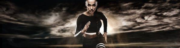 Stark idrotts- kvinnasprinter som kör på mörk bakgrund som bär i sportswear Kondition- och sportmotivation löpare royaltyfri fotografi