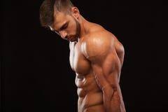 Stark idrotts- man - konditionmodell som visar hans perfekt som isoleras tillbaka på svart bakgrund med copyspace Royaltyfria Foton