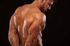 Stark idrotts- man - konditionmodell som visar hans perfekt som isoleras tillbaka på svart bakgrund med copyspace Royaltyfri Foto