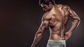 Stark idrotts- mankonditionmodell som poserar tillbaka muskler med trice Arkivbilder
