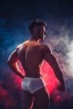 stark kroppsbyggare Man med den perfekta abs, skuldror, biceps, triceps och bröstkorgen, personligt böja för konditioninstruktör  Arkivbilder
