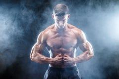 Stark kroppsbyggareman med perfekt abs, skuldror, biceps, triceps, bröstkorg Arkivbild