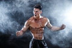 Stark kroppsbyggareman med perfekt abs, skuldror, biceps, triceps, bröstkorg Arkivbilder