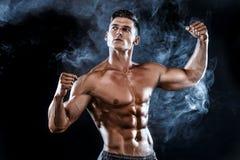 Stark kroppsbyggareman med perfekt abs, skuldror, biceps, triceps, bröstkorg Arkivfoto