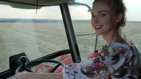 Stark kvinna bak hjulet av skördetröskan i fält i brödskördsäsong lager videofilmer