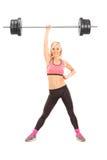 Stark kvinna som lyfter en vikt med en hand Arkivbild