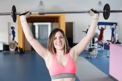 Stark kvinnatyngdlyftning på se för idrottshall Royaltyfri Foto