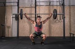 Stark lyftande stång för ung man med vikt i idrottshallen royaltyfria foton